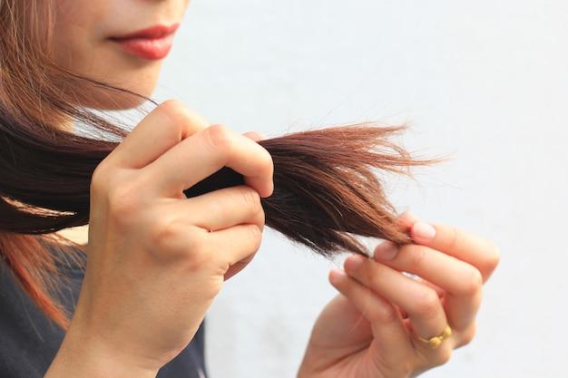 Kobieta patrzeje uszkadzających rozszczepiających końcówki włosy