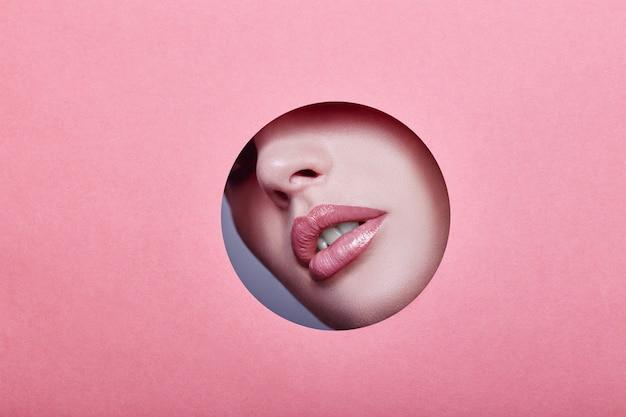 Kobieta patrzeje w dziurze, jaskrawy piękny makeup