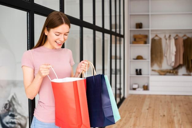 Kobieta patrzeje w papierowe torby