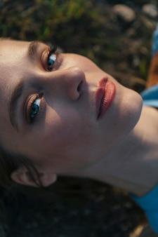 Kobieta patrzy na aparat z jasną twarz i niebieskie oczy