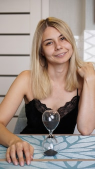 Kobieta patrzy na camers i uśmiecha się, koncepcja czasu. jest w jasnej kuchni i czeka. klepsydra na stole