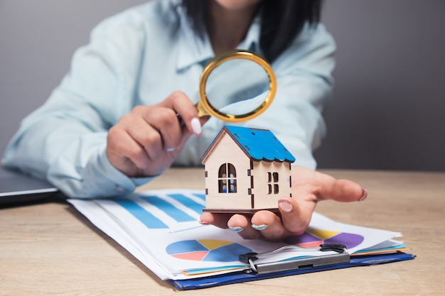 Kobieta patrzy na dom przez lupę i na papier stołowy i dane