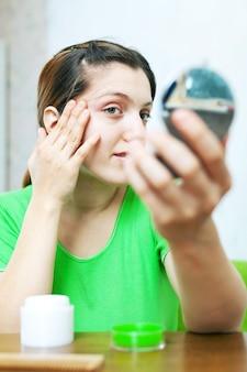 Kobieta patrzy na jej skórę