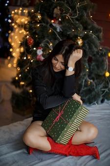 Kobieta patrzy na łóżko i trzyma prezent