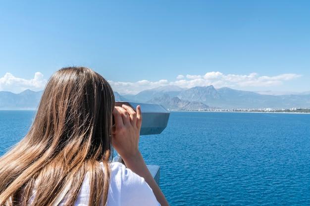Kobieta patrzy na morze, na piękną zatokę i wyspy przez lornetkę, widok z tyłu. podróż i turystyka