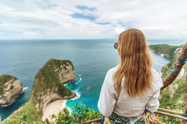 Kobieta patrzy na plażę kelingking na wyspie nusa penida bali w indonezji