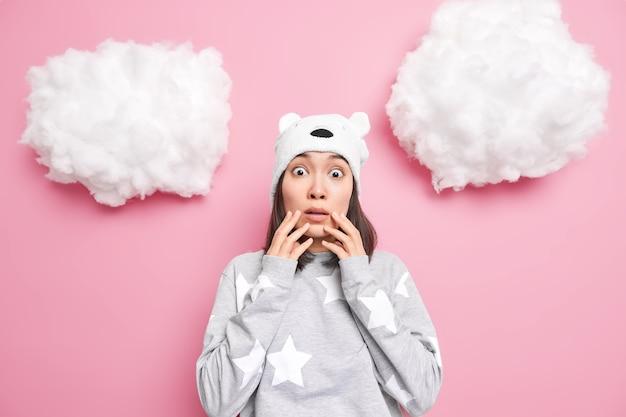 Kobieta patrzy na świadków okropna scena ubrana w piżamę nie może uwierzyć, że jej oczy pozują w środku na różowo