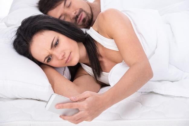Kobieta patrzy na telefon, podczas gdy jej mąż śpi.