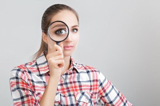Kobieta patrzy przez szkło powiększające