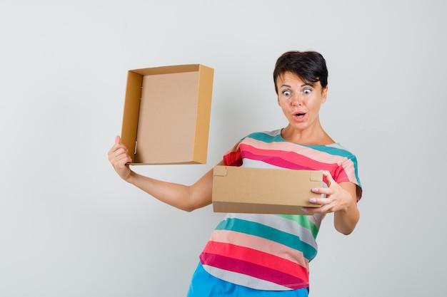 Kobieta patrzy w karton w t-shirt w paski, spodnie i wygląda na zaskoczoną.