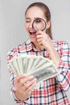 Kobieta patrzy w lupę na banknotach dolarowych