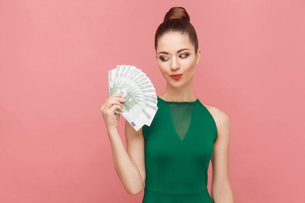 Kobieta patrzy z pożądaniem na pieniądze