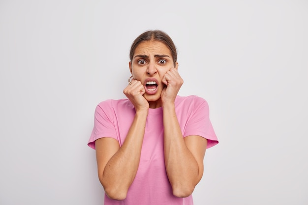 Kobieta patrzy z przerażonym wyrazem przerażenia reaguje na coś nieprzyjemnego ubrana w swobodną różową koszulkę na białym tle