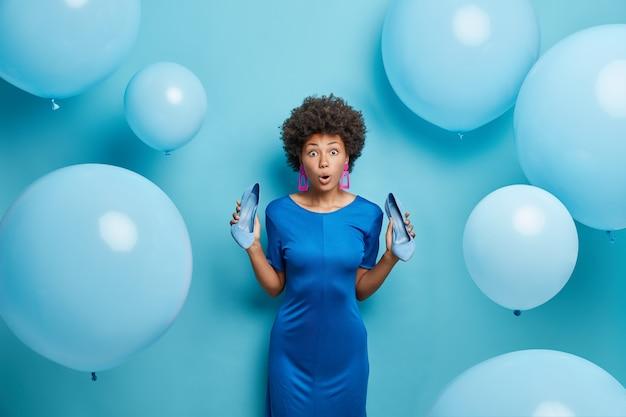 Kobieta patrzy zachwycona wybiera strój na specjalną okazję, aby mieć randkowe pozy w pomieszczeniu na latających balonach izolowanych na niebiesko