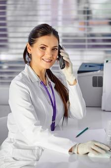 Kobieta pediatra kobieta w garniturze przy użyciu telefonu podczas pracy, konsultując się przez telefon online. siedzi przy biurku z komputerem pc