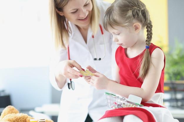 Kobieta pediatra podając małą dziewczynkę blister z pigułkami w klinice leczenia farmaceutycznego