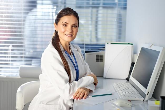 Kobieta pediatra siedzi w miejscu pracy, uśmiechając się, mając stetoskop na szyi. koncepcja medycyny i opieki zdrowotnej