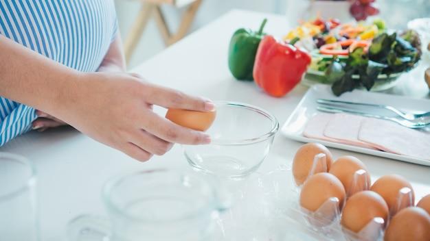 Kobieta pęka jajko w puchar