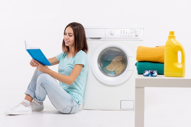 Kobieta pełna strzał czytanie w pobliżu pralki