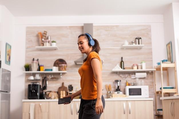 Kobieta pełna szczęścia tańczy w kuchni przy śniadaniu