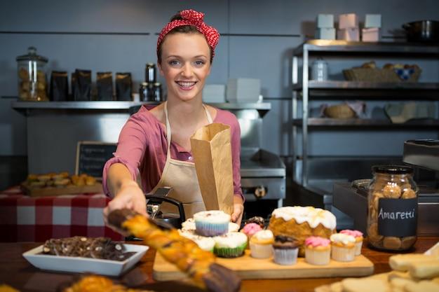 Kobieta personelu pakowania słodkiej żywności w papierowej torbie
