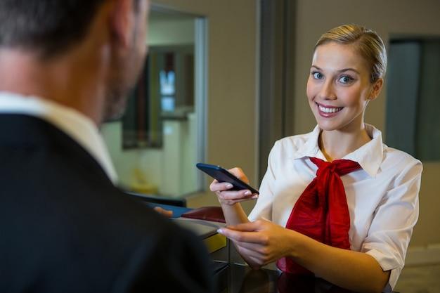 Kobieta personelu skanowania karty pokładowej z telefonem komórkowym