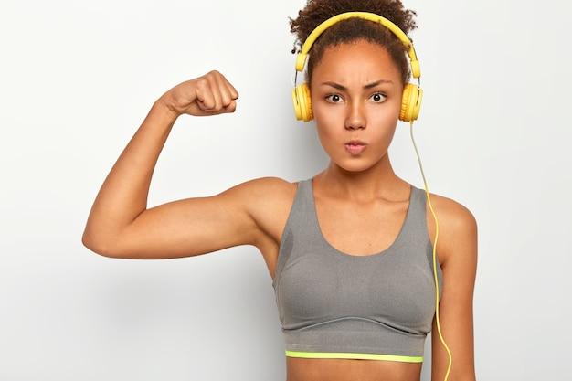 Kobieta pewna siebie o poważnym wyrazie twarzy, podnosi rękę, pokazuje bicepsy, słucha muzyki przez nowoczesne słuchawki, ma sesję cardio.