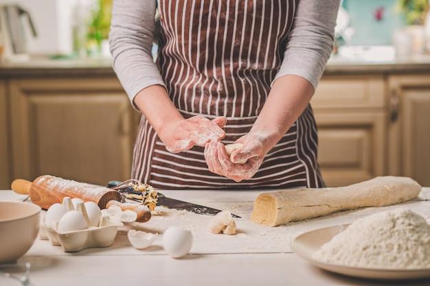 Kobieta piec ciasta. cukiernik robi desery. robienie bułek. ciasto na stole. zagnieść ciasto. kobieta w pasiastym fartuchu gotuje w kuchni