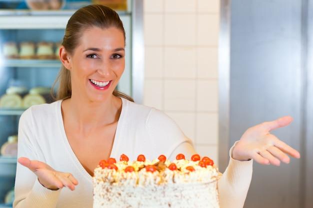 Kobieta piekarz lub cukiernik z tortem