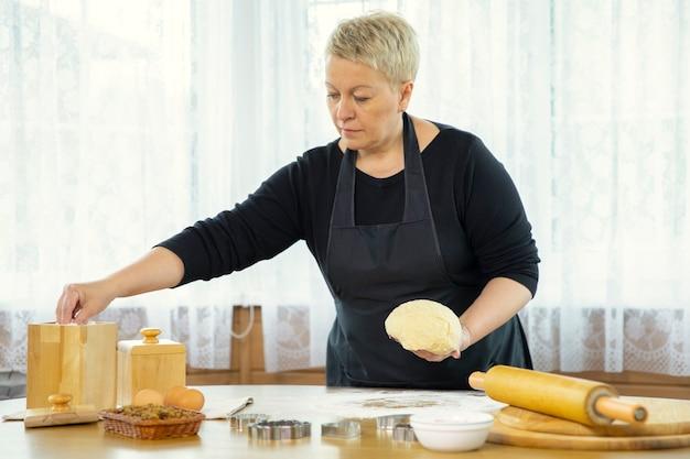 Kobieta piekarz posypuje mąkę na stole, wyrabiając ciasto drożdżowe