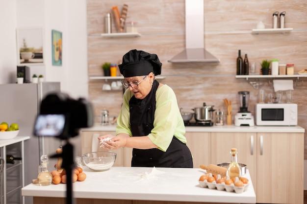 Kobieta piekarz prezentuje przepis podczas nagrywania samouczka dla mediów społecznościowych