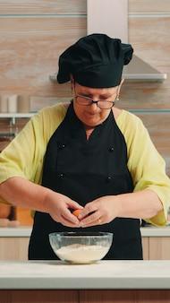 Kobieta piekarz rozbija jajka na mąkę według tradycyjnej receptury w domowej kuchni. emerytowany starszy kucharz z bonete, mieszający ręcznie, ugniatający składniki ciasta w szklanej misce do pieczenia domowego ciasta