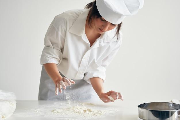 Kobieta piekarz rozwałkowuje ciasto pracując z mąką