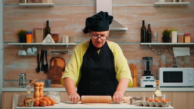Kobieta piekarz toczenia ciasta w domu przed kamerą wyjaśniając krok po kroku przepis. emerytowany bloger szef kuchni wykorzystujący technologię internetową komunikujący się w mediach społecznościowych za pomocą sprzętu cyfrowego