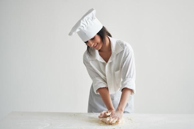 Kobieta piekarz w mundurze kucharza pracuje z produktami z mąki ciasta