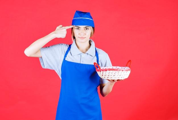 Kobieta piekarz w niebieskim fartuchu trzyma kosz chleba z czerwonym ręcznikiem w środku i wygląda na zdezorientowaną i zamyśloną