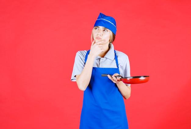 Kobieta piekarz w niebieskim fartuchu trzyma patelnię tefal i wygląda na zdezorientowaną i zamyśloną