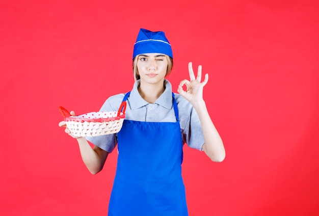 Kobieta piekarz w niebieskim fartuchu trzymająca kosz chleba z czerwonym ręcznikiem w środku i pokazująca znak przyjemności