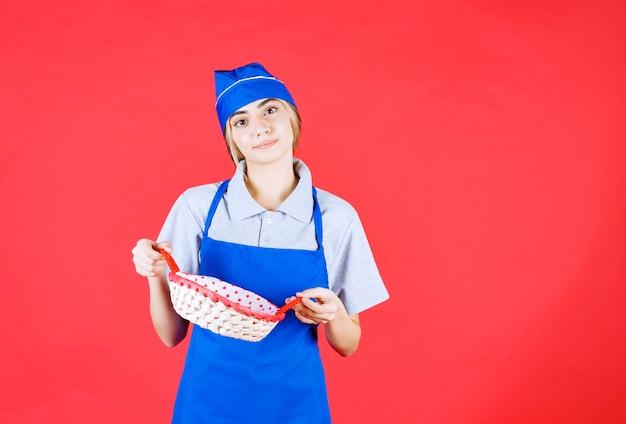 Kobieta piekarz w niebieskim fartuchu trzymająca kosz chleba z czerwonym ręcznikiem w środku