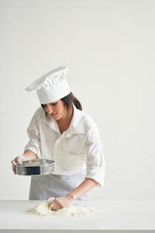 Kobieta piekarz w ubraniach szefów kuchni profesjonalna praca z kuchnią ciasta
