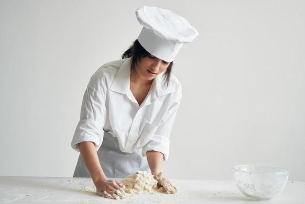 Kobieta piekarz wyrabia ciasto na stole praca zawodowa