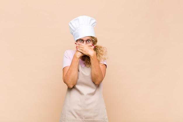Kobieta piekarz zakrywająca usta rękami z zszokowanym, zdziwionym wyrazem twarzy