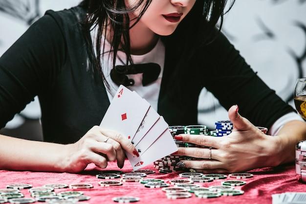 Kobieta piękna młoda udana gra hazardowa w kasynie przy stole z kartami, żetonami i alkoholem zbliżenie