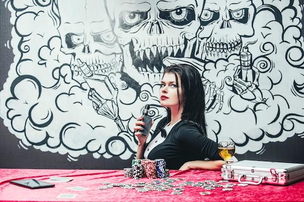 Kobieta piękna młoda udana gra hazardowa w kasynie przy stole z kartami, żetonami i alkoholem
