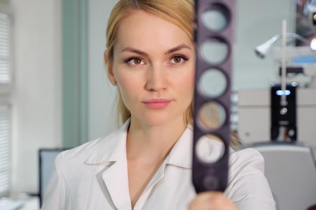 Kobieta piękna okulista z urządzeniem okulistycznym w gabinecie.