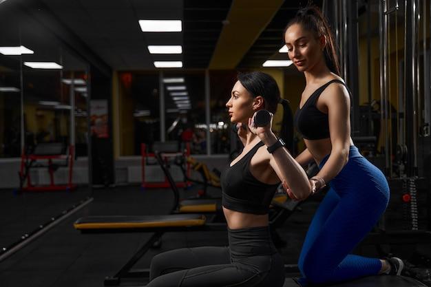 Kobieta piękna sportowiec ćwiczenia z hantlami w klubie fitness