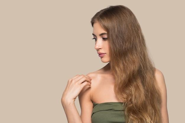 Kobieta piękna twarz zdrowa. piękna młoda modelka dotykając się. kolor tła. brązowy