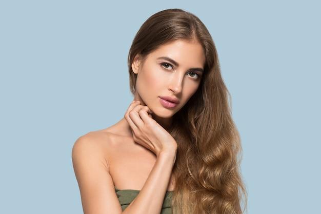 Kobieta piękna twarz zdrowa. piękna młoda modelka dotykając się. kolor tła. niebieski