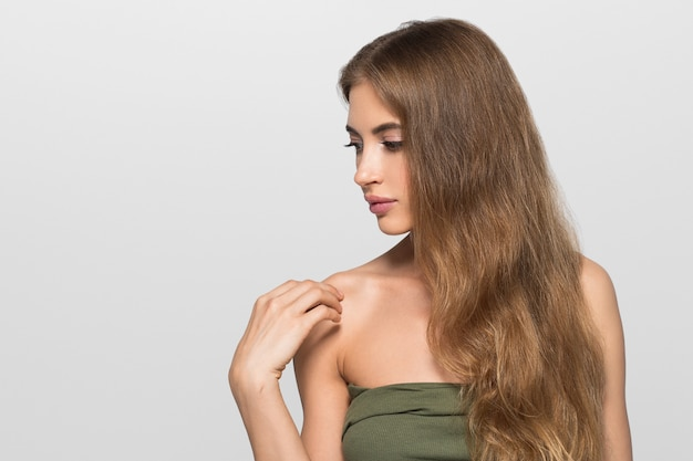 Kobieta piękna twarz zdrowa. piękna młoda modelka dotykając się. kolor tła. szary