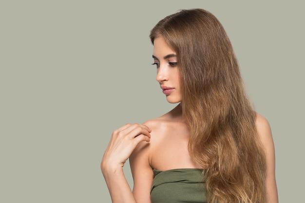 Kobieta piękna twarz zdrowa. piękna młoda modelka dotykając się. kolor tła. zielony